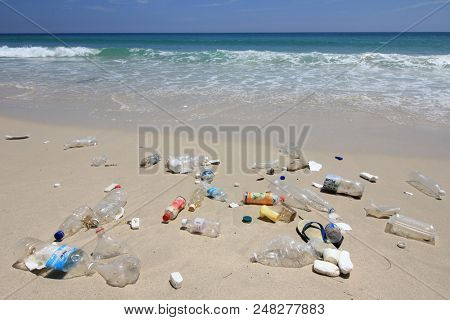 KUDAT, MALAYSIA - CIRCA JUNE 2018: Plastic bottles, bags and other trash washed up on beach