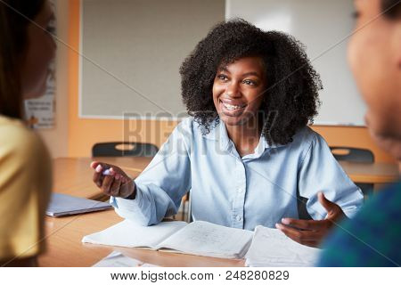 Female High School Tutor With Two Students At Desk In Seminar