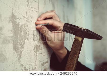 Close-up Of Handyman Hammering A Nail In Board. Concept Of Repair And Renovation. Guy Hammering A Na