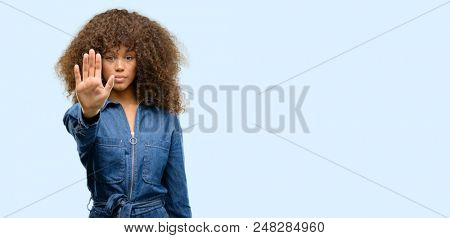 African american woman wearing blue jumpsuit annoyed with bad attitude making stop sign with hand, saying no, expressing security, defense or restriction, maybe pushing