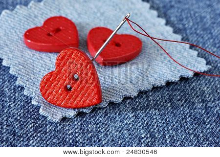 Tiny heart shaped buttons with needle and thread on denim fabric with copy space.  Macro with shallow dof.