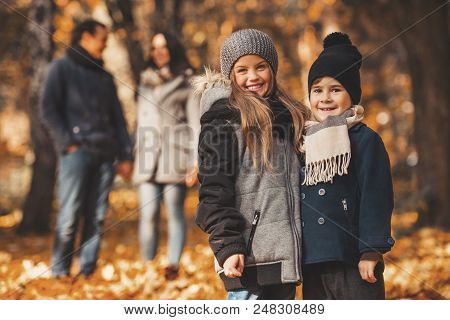 Young Family Of Four Have Fun In Autumn Park. Happy Time Spending Outdoor Concept. Young Family Havi