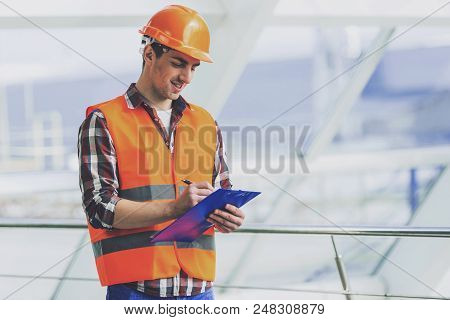 Industrial Engineer In Yellow Helmet And Vest Makes Notes On Tablet. Modern Construction And Enginee