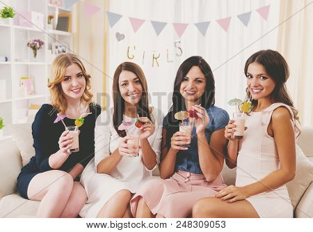 Young Beautiful Girls Have Fun And Drinks Cocktails At Home Party. Celebration At Home. Enjoing Part
