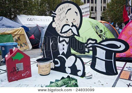 LONDON, UK -OCTOBER 31: Banksy's bankrupt banker begging for change on Occupy London site near St. Paul's Cathedral on October 31, 2011 in London.