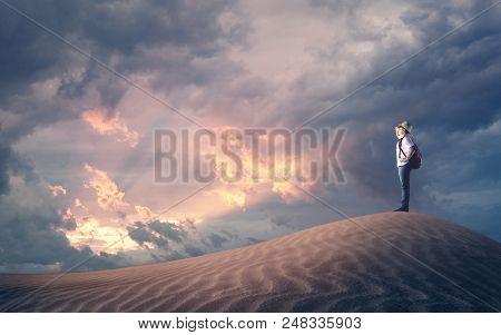 Traveler Kid On A Sand Dune Loonking Up To Horizon At Sunset .