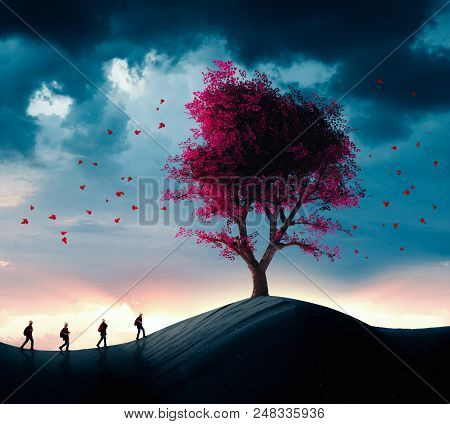 Group Of Travelers Walking In The Desert To A Big Tree.