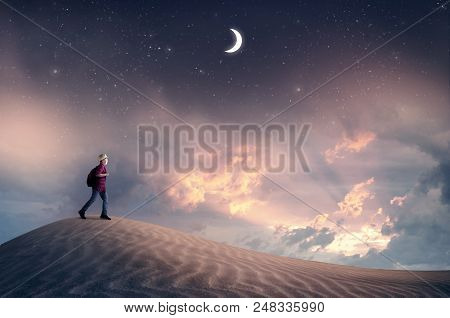 Traveler Explore The Desert At Sunset When Passing From Day To Night.