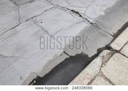 Damaged City Street - Cracks And Patches On Blacktop.