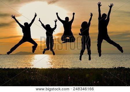 Silhouette Of Friends And Teamwork Jumping On Beach During Sunset Time For Success Business.  Lifest