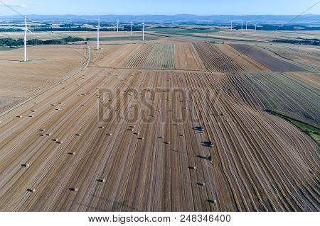 Aerial View On The Windmills On The Field With Hay Bales And Balers Working