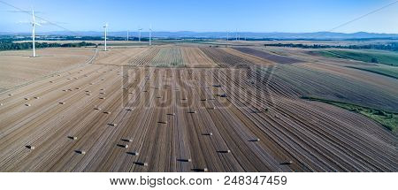 Panoramic View On The Windmills On The Field With Hay Bales And Balers Working