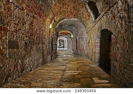 Colle di Val d'Elsa, Siena, Tuscany, Italy: the picturesque covered alley Via delle Volte, a medieval dark passage in the old town poster
