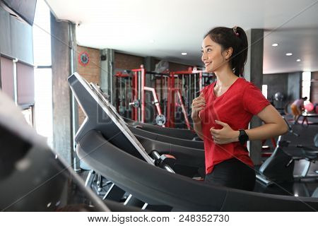 Asian Women Running Sport Shoes At The Gym While A Young Caucasian Woman Is Having Jogging On The Tr