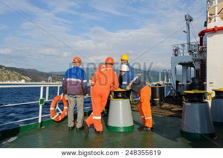 Seamen Standing On Deck Of Cargo Vessel