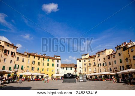 LUCCA, ITALY - MAY 31, 2018: Tourists at Piazza dell Anfiteatro, a popular tourist attraction and one of the most beautiful squares in Lucca following the shape of the old Roman amphitheater