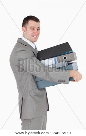 Portrait of a young businessman holding a stack of binders against a white background
