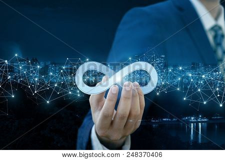 Businessman Shows Sign Of Infinity On The Background Of The City. The Concept Of Unlimited Internet.