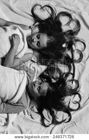 Pajama Party And Childhood Concept. Girls Lie On White And Pink Bed Sheets. Kids With Smiling Faces
