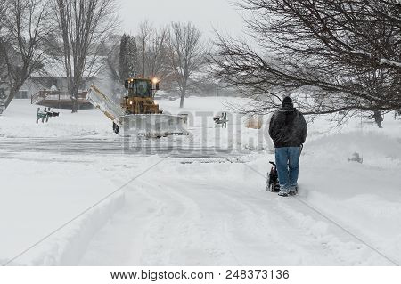 Chanhassen, Mn - April 14, 2018: Owners Plow Driveways And City Clears Street During April Mn Blizza
