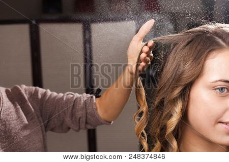 hairdresser fixing a coiffure with waves of a young beautiful girl using a hair spray in a beauty salon. concept of professional stylist studying poster