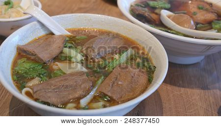 Family enjoy the beef noodles in restaurant