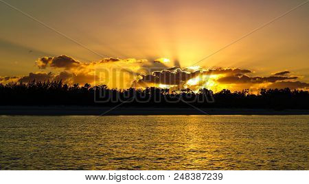 A Striking Inspirational Golden Colored Cloudy Sunrise Seascape Featuring Bold Crepuscular Rays (sun