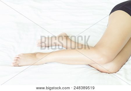 Closeup Woman Legs With Sleeping On White Bed, Beauty And Skin Care Concept, Selective Focus