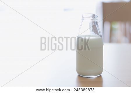 Closeup Bottle Of Millk On Wood Table Background With Over Light Reflex From Out Door For Healthy Dr