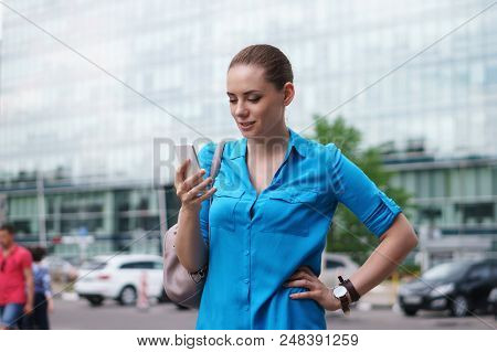 Young Attractive Girl Is Holding A Cell Phone. She Looks At The Smartphone Screen And Smiles. Good N