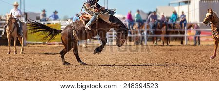 Cowboy Riding A Bucking Bronco Horse In A Competition At A Country Rodeo