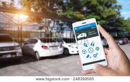 Hand Holding Smart Phone And Application Dashboard With Blur Car Parking Background.