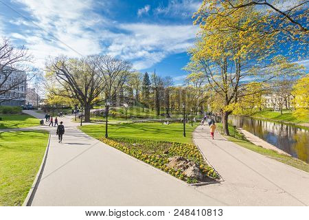 Riga, Latvia - May 06, 2017: View On  Pathways With Blossom Trees, Bushes And Walking  People In The