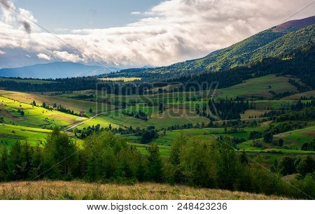 Beautiful Mountainous Countryside On A Cloudy Day. Wonderful Landscape In Early Autumn. Row Of Trees