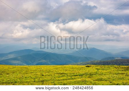 Grassy Alpine Meadow In Cloudy Weather. Beautiful Landscape Of Carpathian Mountain In The Distance.