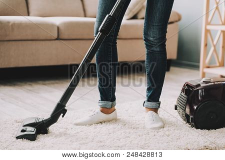 Close Up. Woman In Jeans Cleans Carpet With Vacuum Cleaner. Professional Janitor Vacuuming White Car