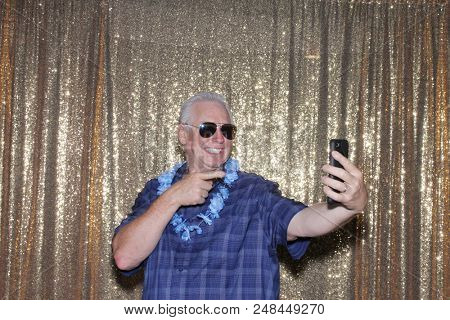 Selfies picture. A Man in a Photo Booth takes Selfie Photos with his cell phone as his photo is taken in a Photo Booth with a Gold Sequin Background. Photo Fun at Parties and Weddings.
