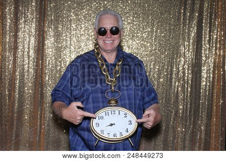 Photo Booth. A Good Looking Man in a Photo Booth with a Gold Clock Necklace against a Gold Sequin Background. Time to Party. Photo Booth Photo.