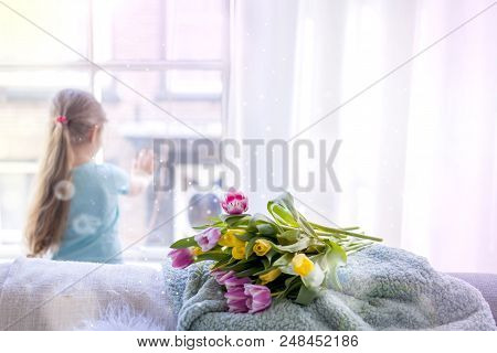 Girl With A Note Of Spring Flowers. At A Cozy House In The Living Room By The Window. Tulips Of Diff