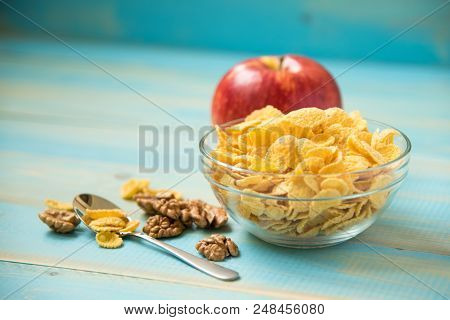 Tasty Cornflakes Witt Walnut And Apple In Glass Bowl On Blue Background. Corn Flakes. Healthy Breakf