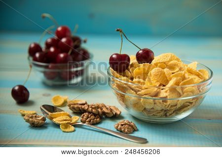 Tasty Cornflakes Witt Walnut And Cherry In Glass Bowl On Blue Background. Corn Flakes