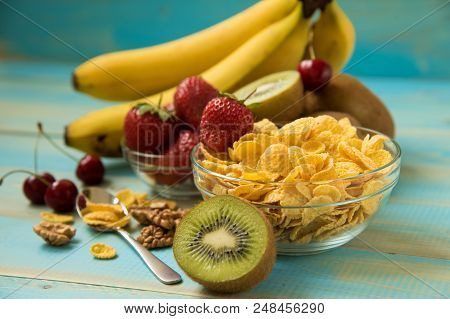 Tasty Cornflakes In Glass Bow With Walnut And Strawberries, Bananas, Kiwi On Blue Background.  Corn