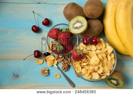 Tasty Cornflakes In Glass Bow With Walnut And Strawberries, Lbananas, Cherry, Kiwi On Blue Backgroun