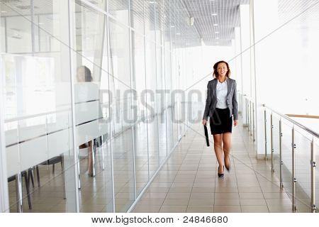 Empresária andando no corredor do escritório