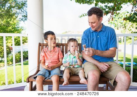 Caucasian Father Sitting With His Mixed Race Chinese and Caucasian Boys Enjoying Ice Cream Cones