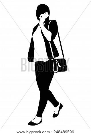 Silhouette Of A Walking Woman In A Trouser Suit And Talking On The Phone