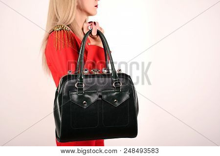 Slender Girl In A Red Jacket And Jeans With A Green Bag Stands Sideways