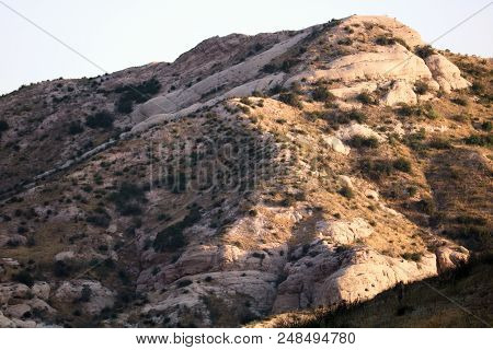 Rock formations formed by earthquakes surrounded by fields of arid chaparral shrubs taken on the San Andreas Fault at a rural plain in Cajon, CA poster