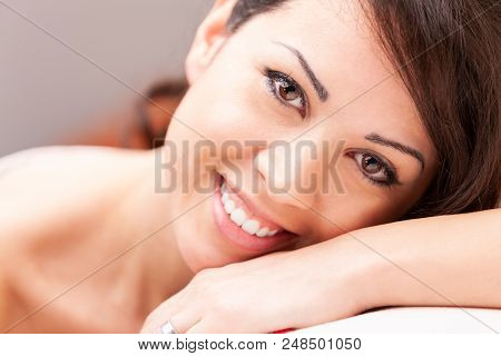 Beautiful Coy Woman Smiling On Her Sofa