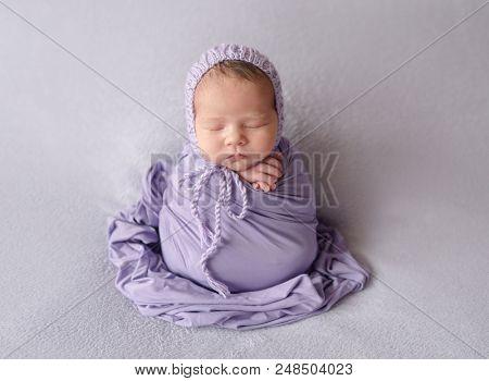 Cute sleeping newborn baby girl in violet